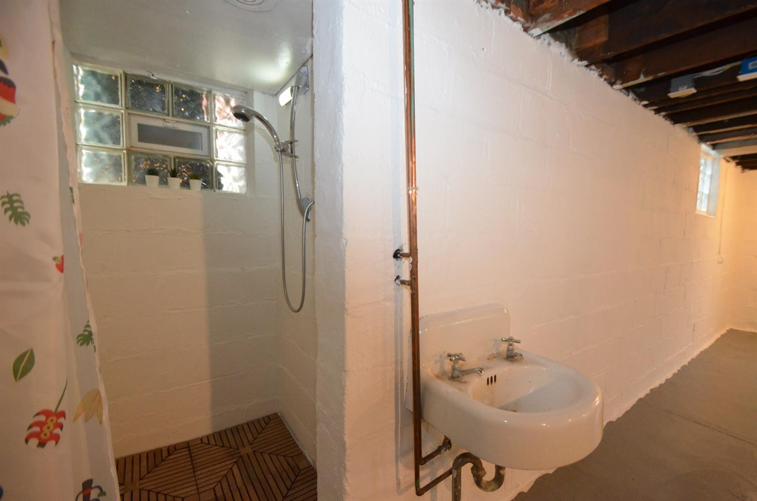 Cute full bath in the basement features this old timey sink and shower.