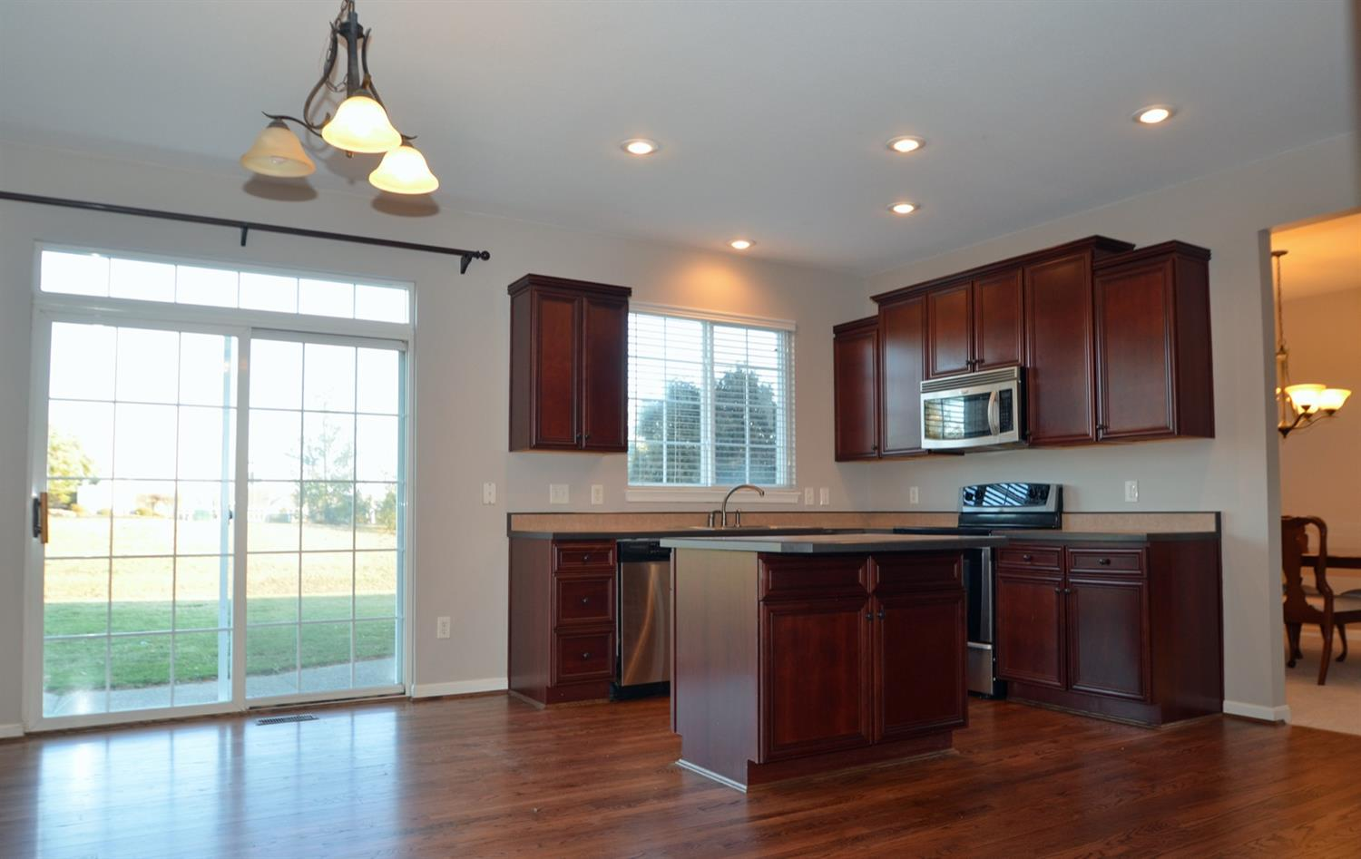 The open plan kitchen features a walkout to the home's patio and yard from the eat-in dining space.