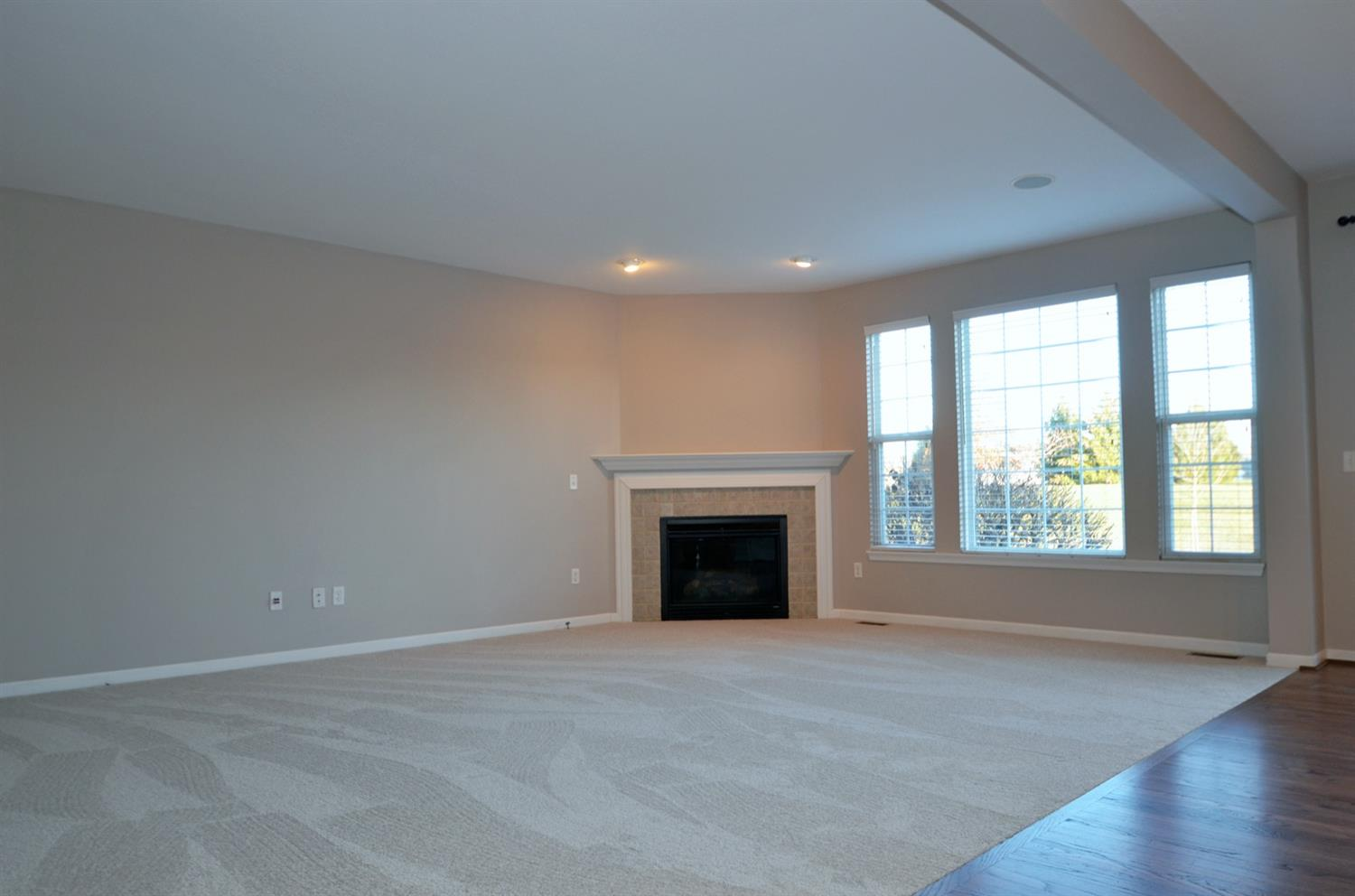 Plenty of light from the oversized windows. Check out the cozy gas corner fireplace and mantel.