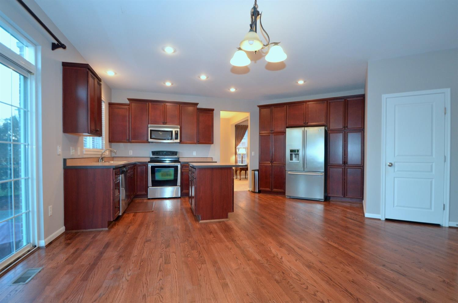 Stainless steel appliances including a large fridge and plenty of storage and pantry space sit atop beautifully refinished hardwood oak flooring.