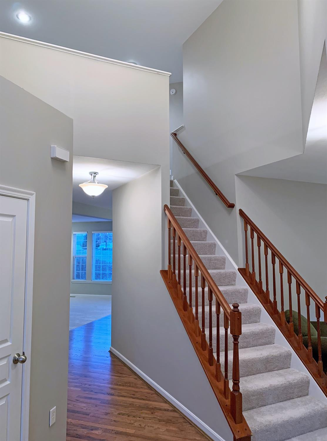 The striking angles of the double-height entry and warm newly refinished hardwood floors welcome you.