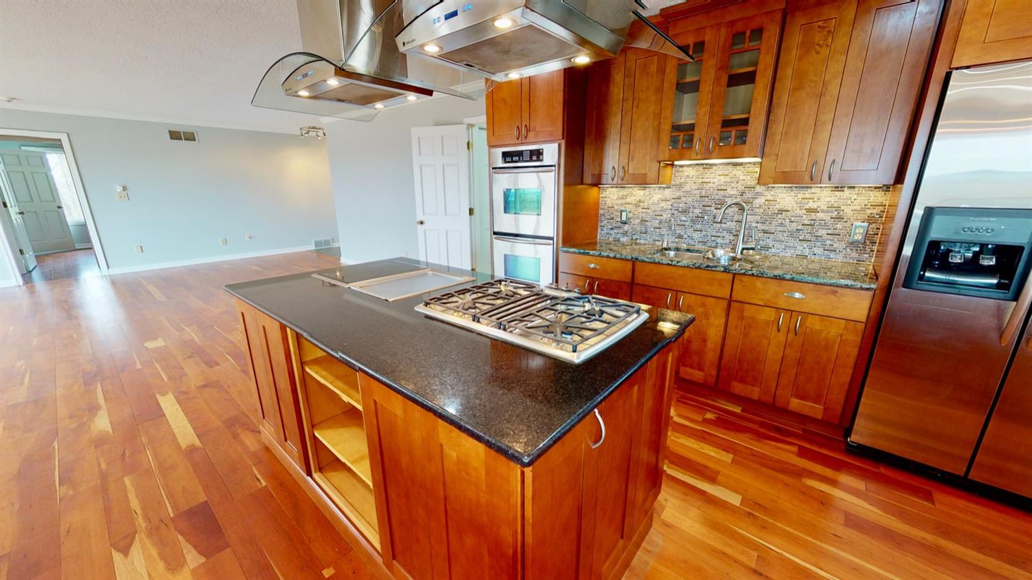Island including upgraded gas cooktop, Induction cooktop and Yaki Grill surround by the Cavaliere Mounted Range Hood