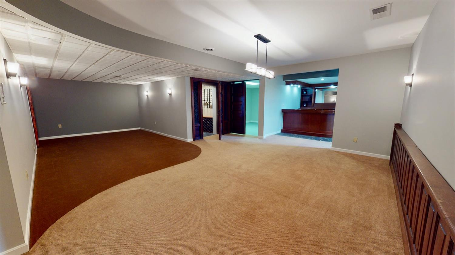 Entrance to billiard and media rooms with access to wine cellar, workout room and full bar complete with sink, refrigerators and dance club.