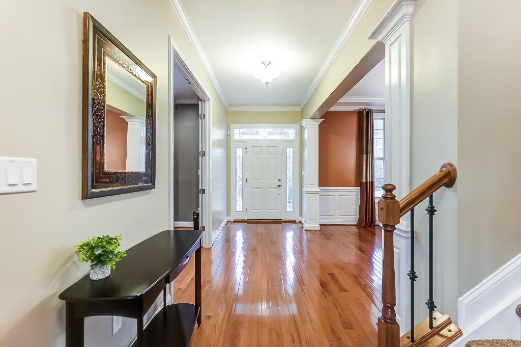 Entry with gleaming hardwood floors; crown molding.