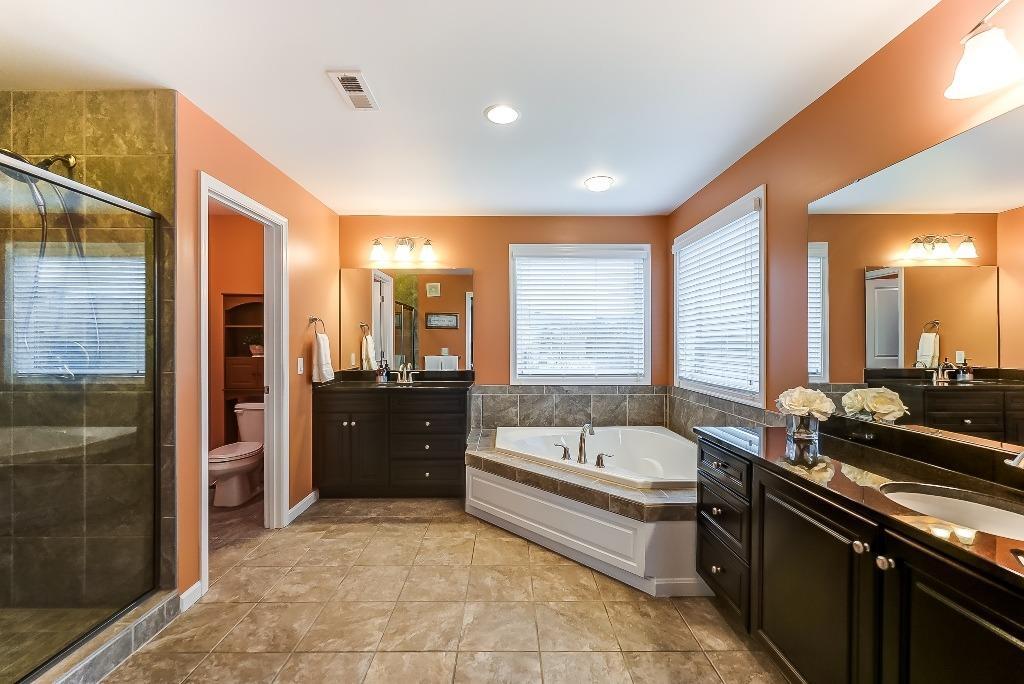 Master bath features double vanities, ceramic tile floor and shower; granite countertops.