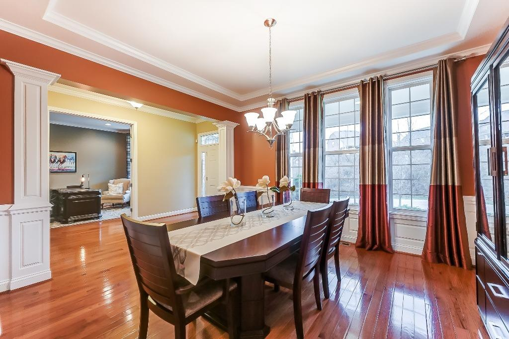 Formal dining room features tray ceiling, crown molding, chair rail and wainscoting.