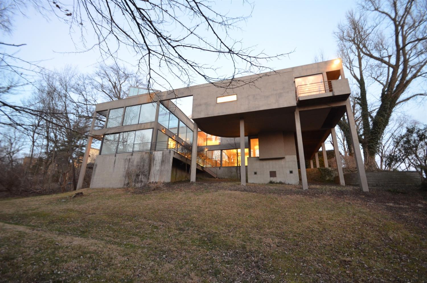 Twilight view of west facade. The steel-framed stucco, glass and wood home is burrowed into the hillside on its public facing and sparsely fenestrated north and east facades whereas its private west and south facades (which in part sit atop tall piers) are open with large expanses of glass to take advantage of its enviable views.