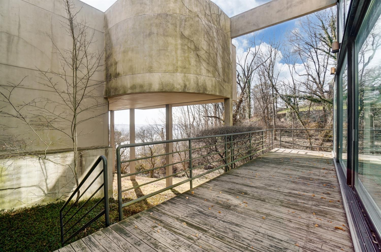 Another deck accessible from the pool atrium provides dramatic architectural and natural views. Stairs leading to large wooded yard.
