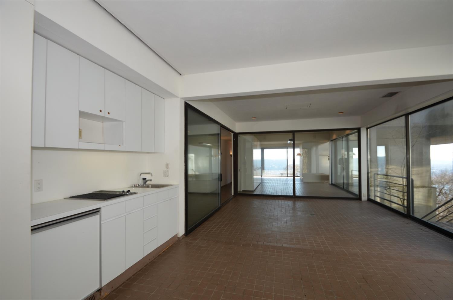 Another view of the poolside entertaining area highlights the kitchenette including a Thermador indoor grille.