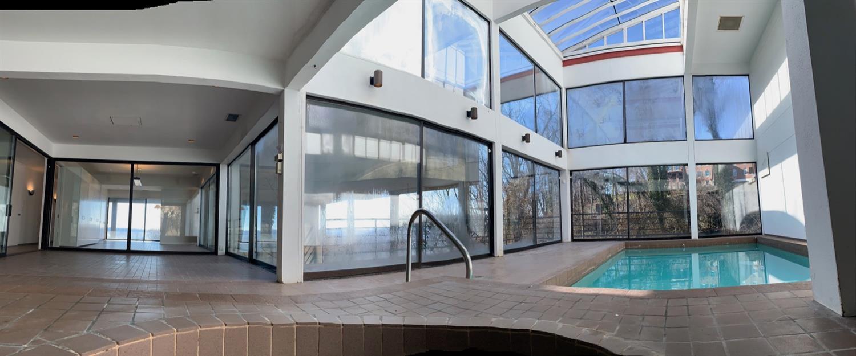 Panoramic photo of pool atrium and poolside entertaining area.