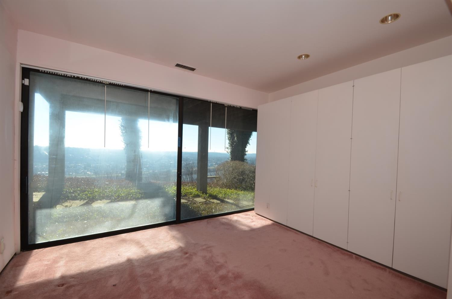 Bedroom 2 features an oversized window/slider facing the riverview, custom closet cabinetry and an ensuite full bath.