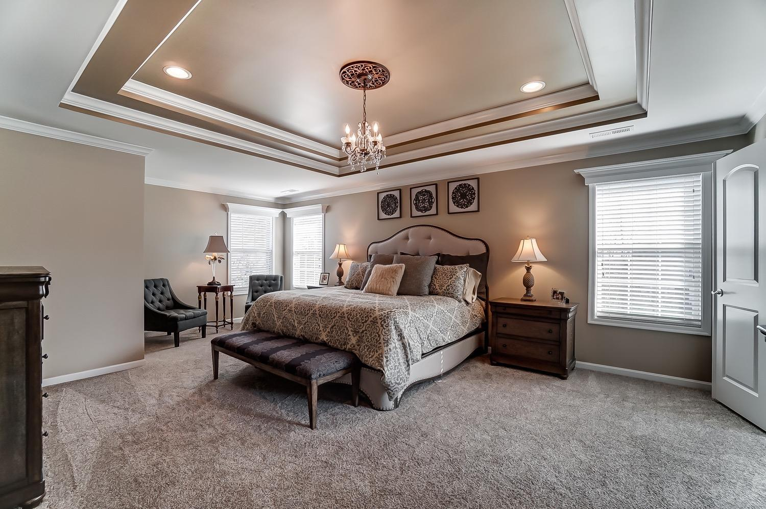 Large master suite with sitting area, double tray ceiling and chandelier.