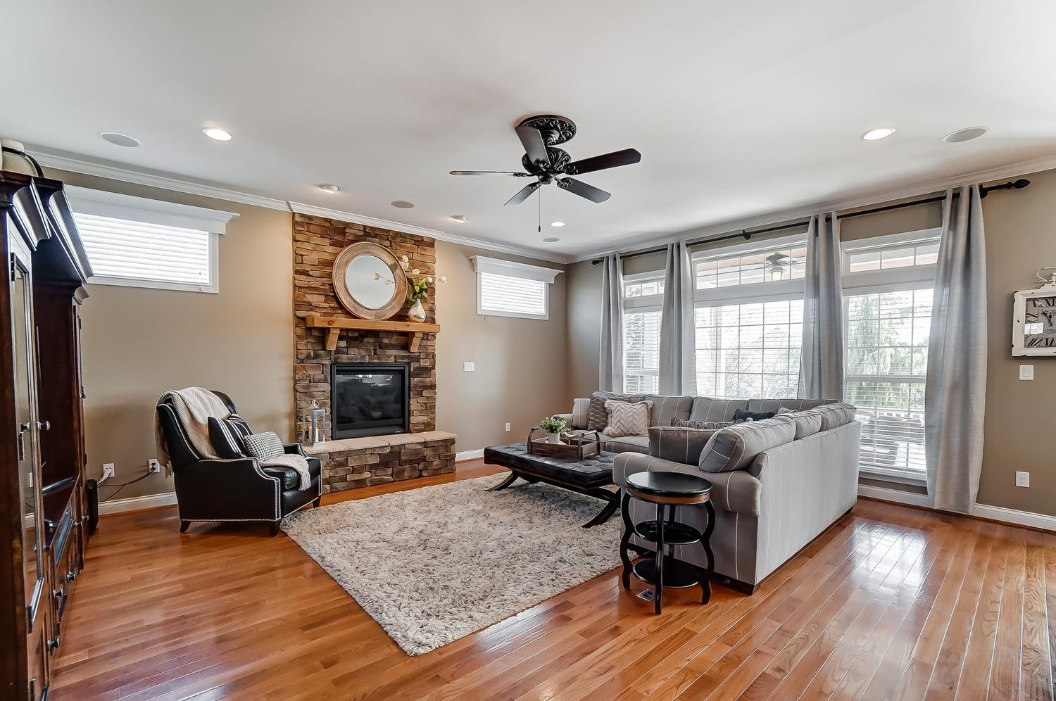 Family room has 10' ceiling, wall of windows, stone fireplace and hardwood floors.