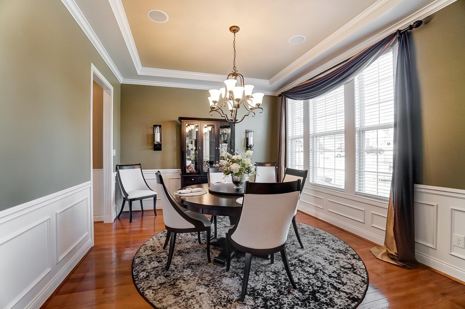 Dining room features tray ceiling, chandelier, and ceiling speakers.