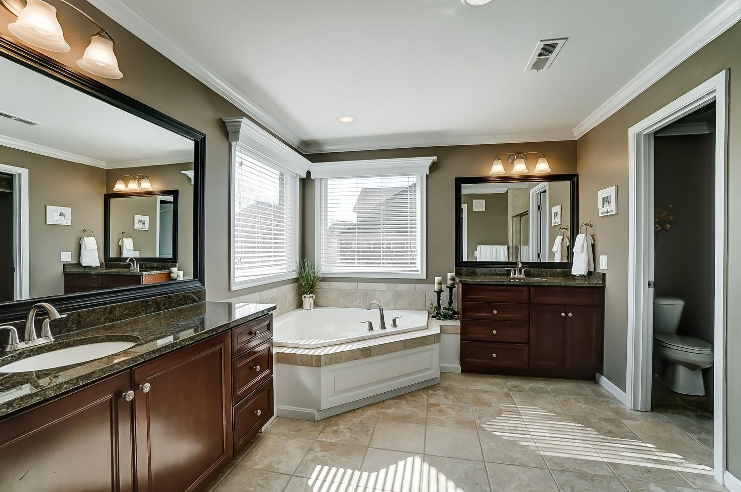 Master bath has soaking tub, double vanities and shower w/ built-in bench.
