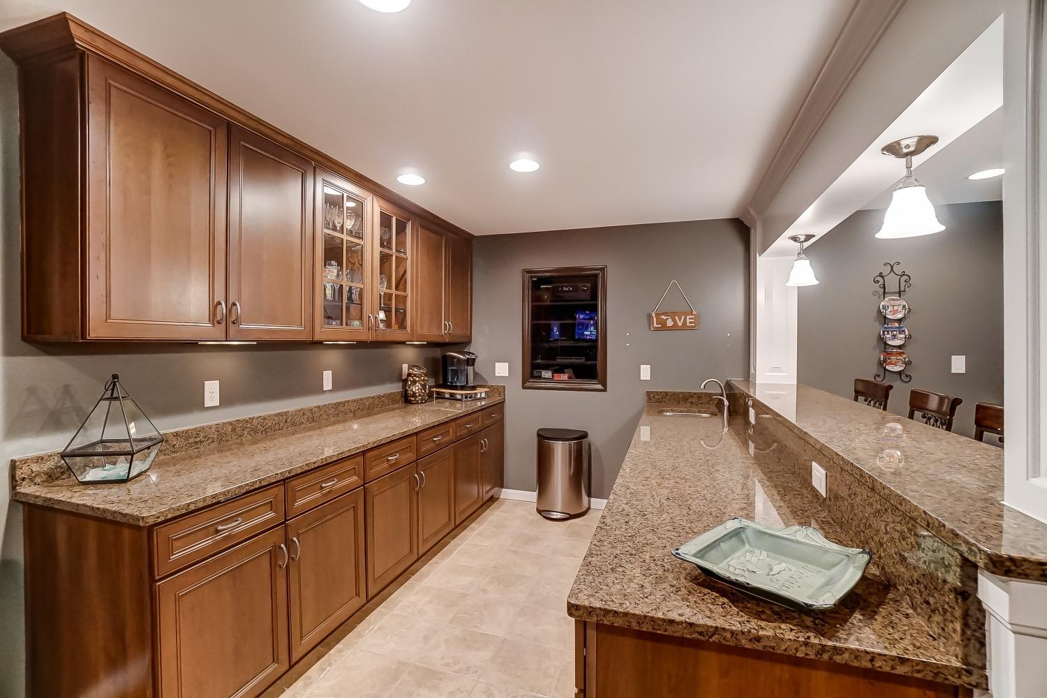 Lots of cabinets, granite countertops and glass-front shelves for electronic components in wall.
