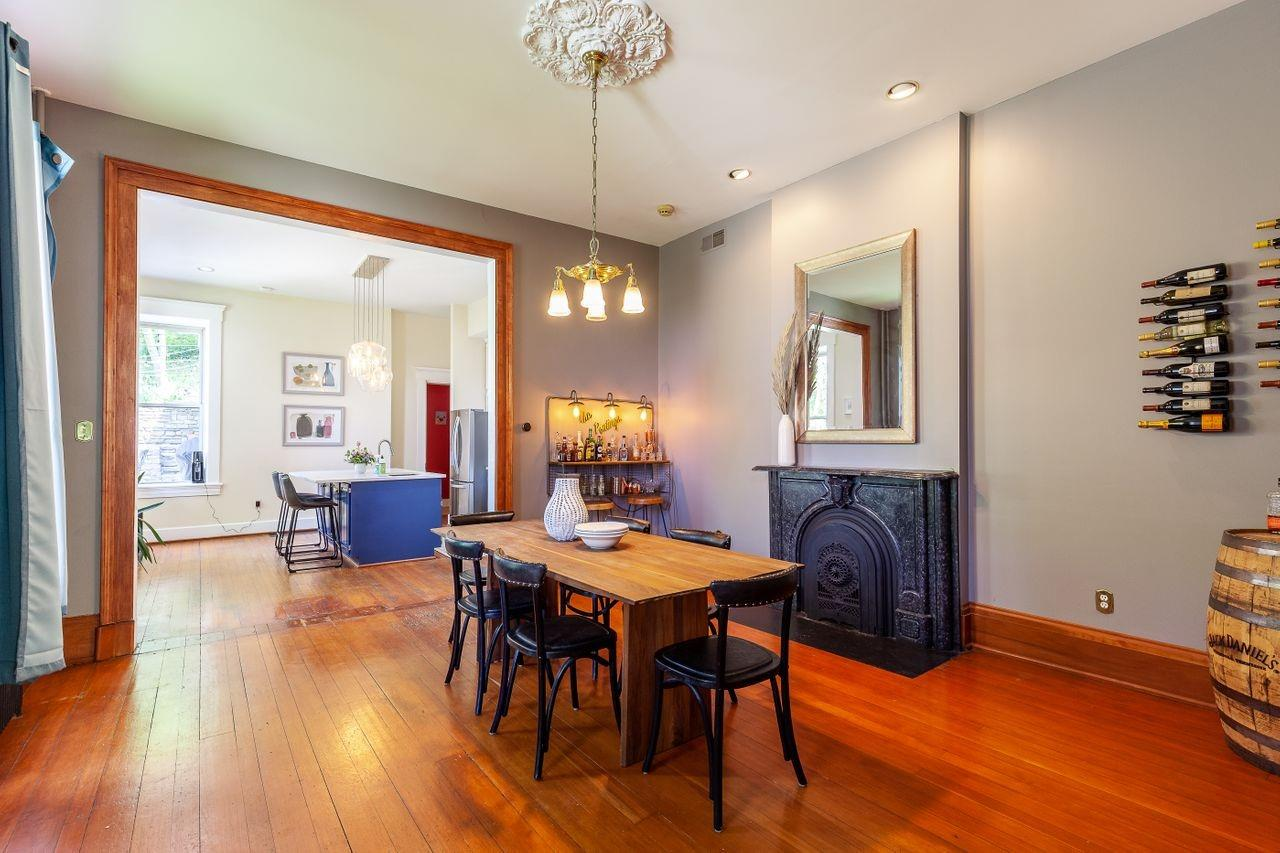 The rooms are spacious with 10+ foot ceiling, original woodwork, and large windows.  The dining room is just off the side entry and opens to the kitchen. Finished include beautiful hardwood floors, simple-chic chandelier, a cast-iron fireplace, and large windows.
