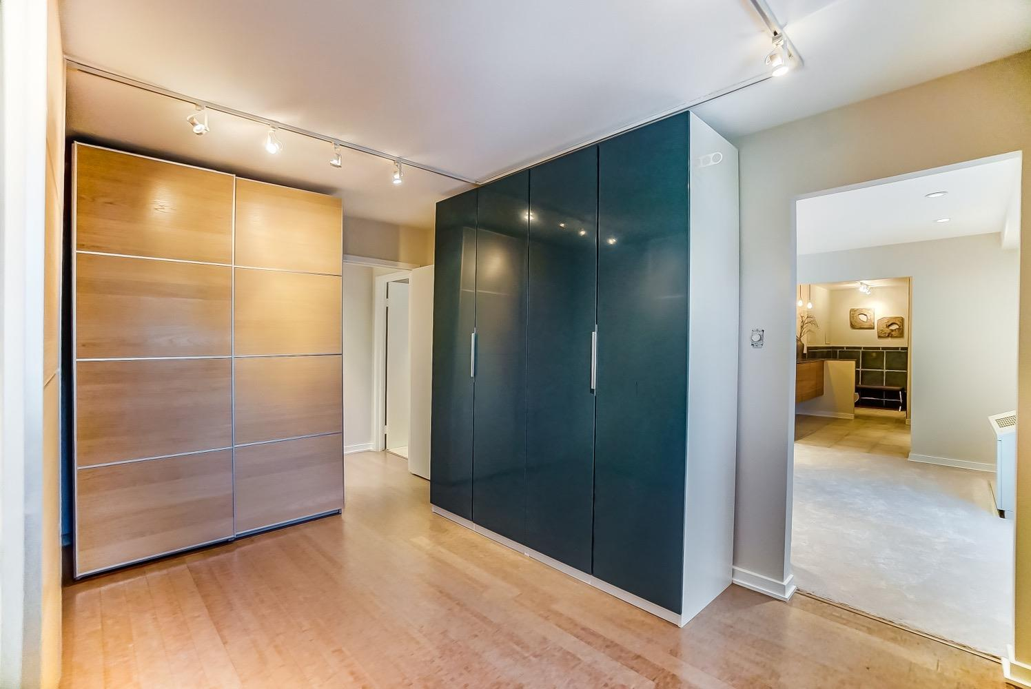 A view into the converted walk-in primary closet. The closet wardrobe units could be relocated to the primary bedroom should someone desire to return the space to a third bedroom.