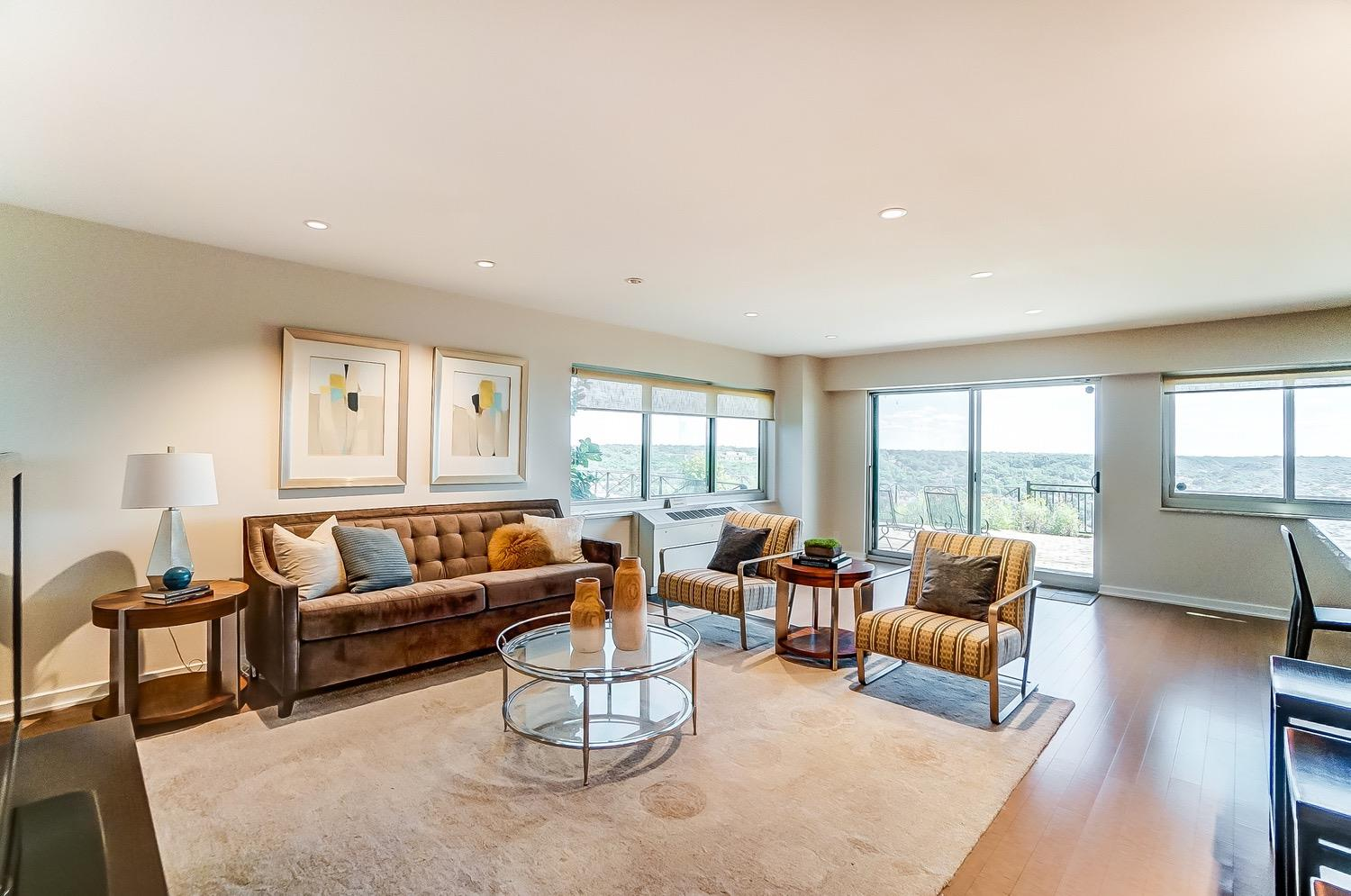 Abundant natural light streams through the oversized newer replacement picture windows and slider and provide an incredible river view and access to the enormous outdoor space. This end unit has windows on 3 sides such as the window on the left. Newer bamboo flooring ad recessed lighting.