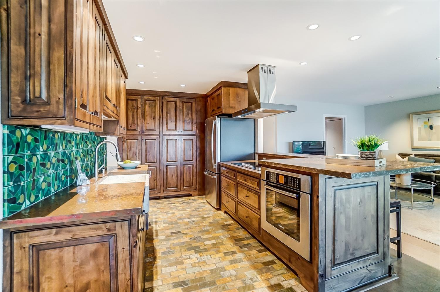 The kitchen features custom wood cabinets and copper countertops throughout, handmade artisan backsplash tile and a heated tile floor.