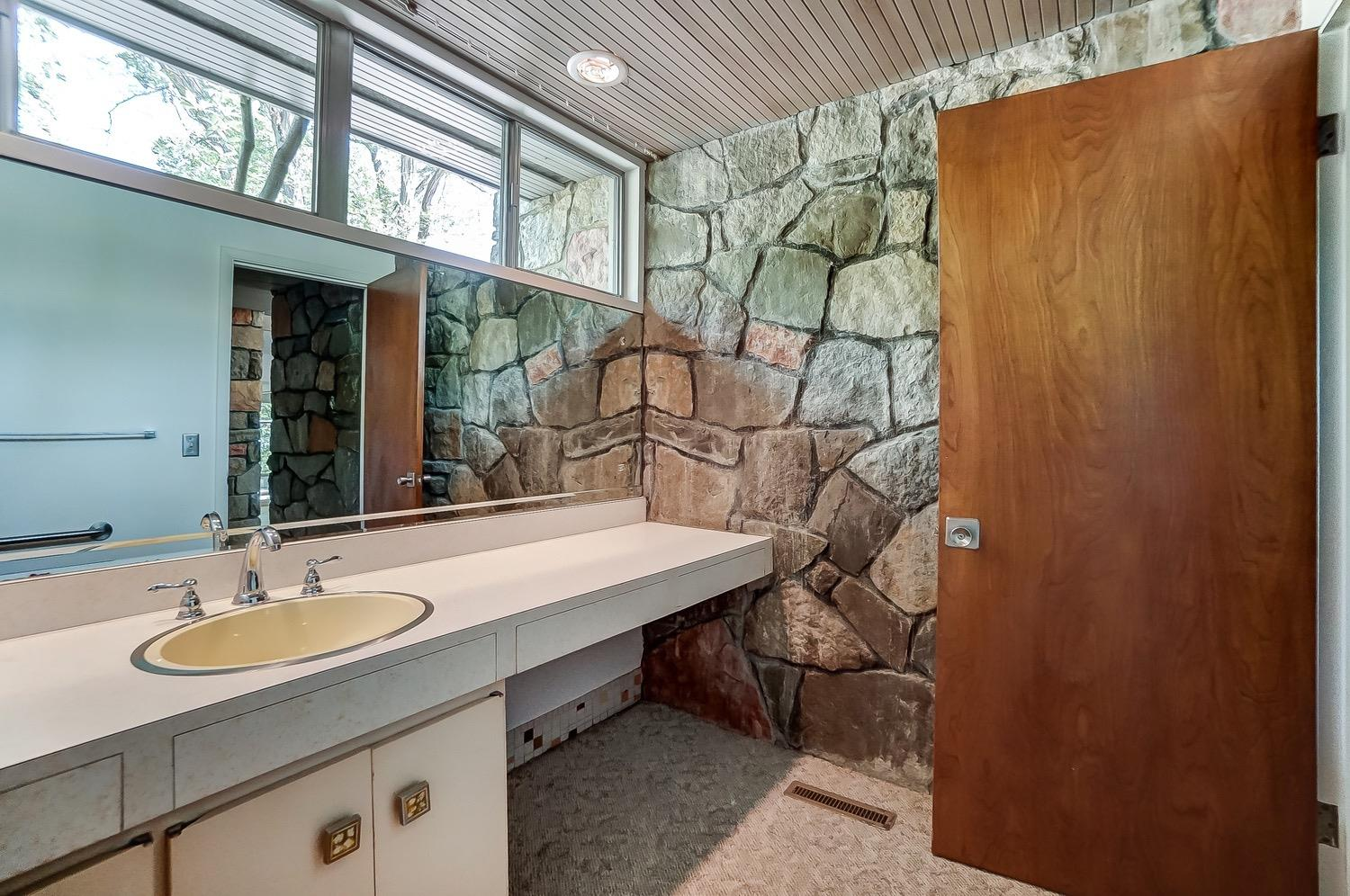 A great contrast of materials is highlighted by the abundant light from the high casement windows. Carpeting over the original mosaic tile floor.
