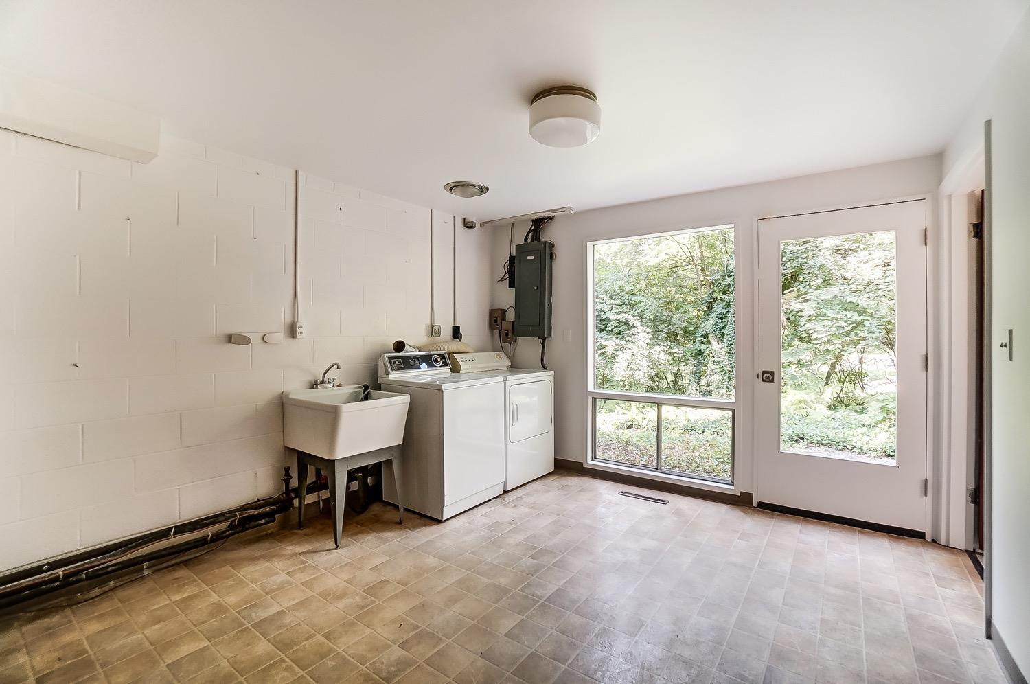 An expansive laundry room with side entry allows for easy access the home's 5th bedroom and full bath.