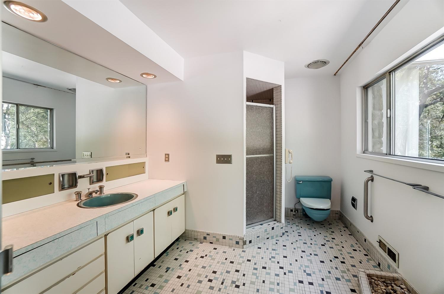 All original blue and green primary bath with mosaic tile, large custom vanity with storage niches and delightful original hardware including the resin door knobs. In the lower right corner of the photo is a peek of the indoor planter beneath the wide picture window. A surprise awaits behind the shower door!