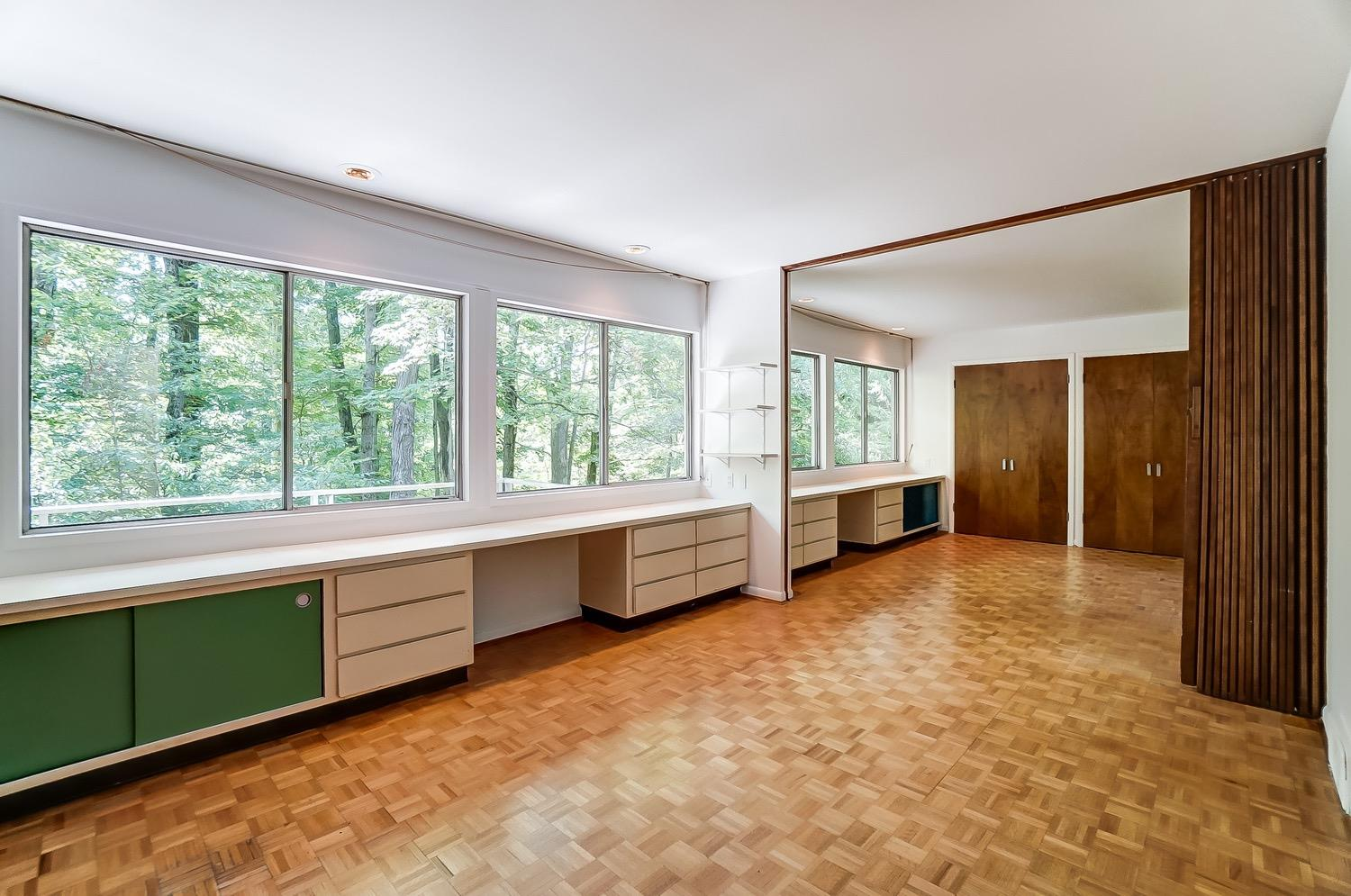 The nearly identical mirror-image bedrooms 2 and 3 are divided by an a wooden accordion sliding wall. The beautiful wood parquet flooring is found throughout the second floor (even under the primary suite bedroom and dressing areas as well as the hallways).