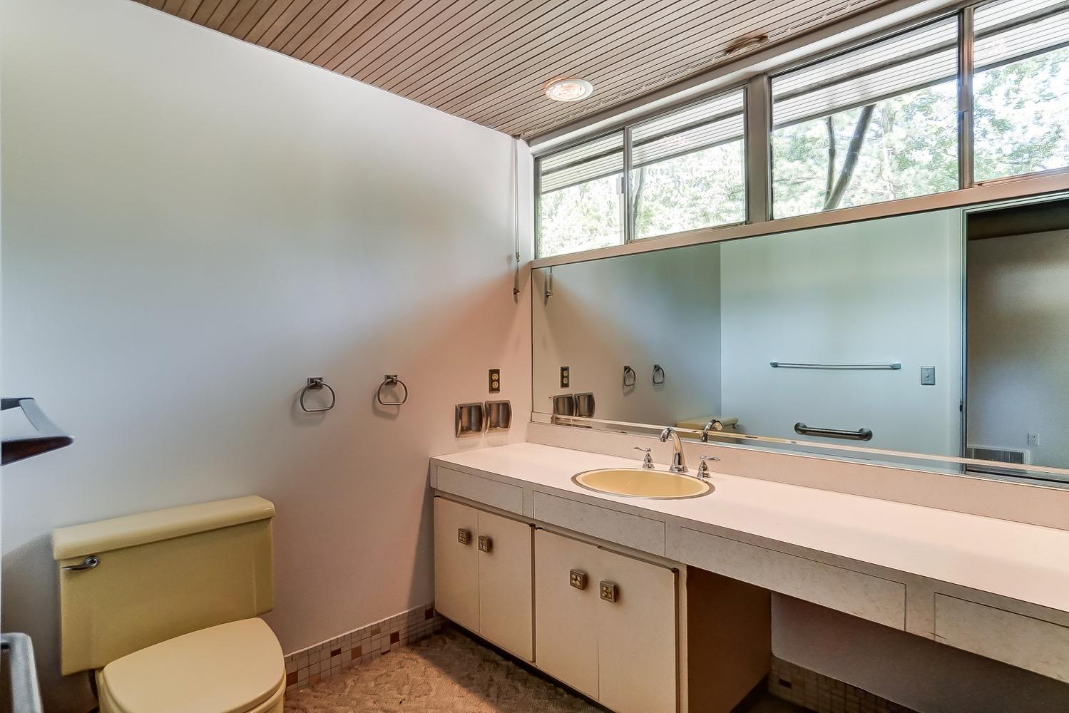 Main level half bath. All original vintage custom vanity, hardware and more of the resin cabinet door knobs.