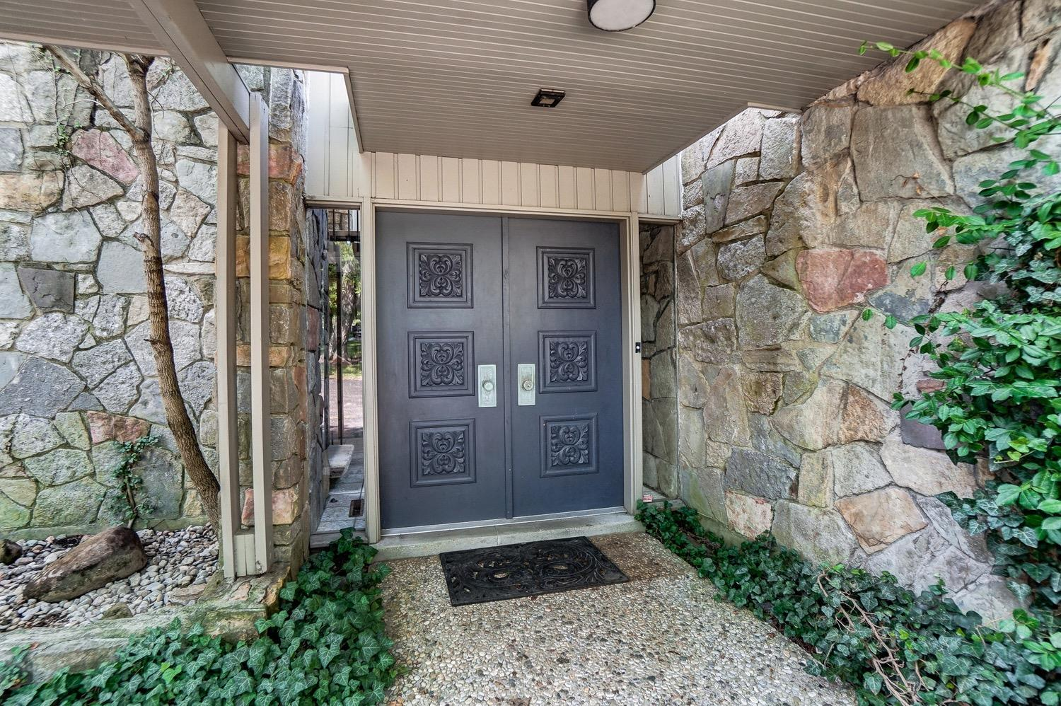 Contrasting stone and wooden board and batten siding welcome you to the home's entry. Note the glass side lights are expertly scribed directly to the edges of the stone walls.