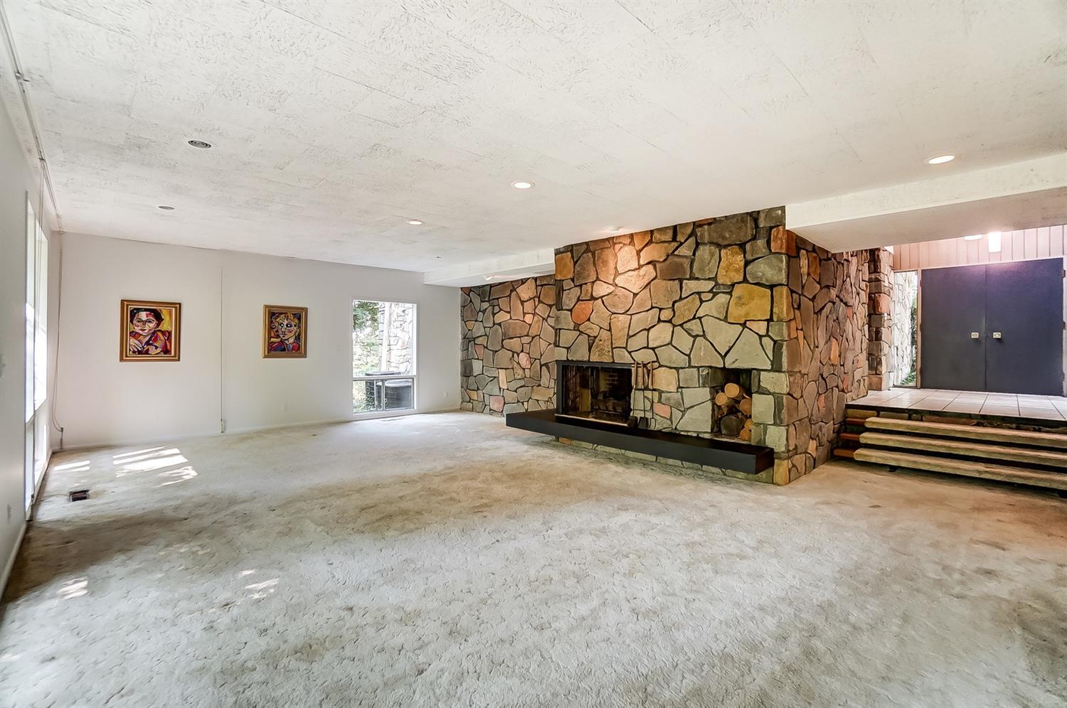 A view of the living area's dramatic stone fireplace. Several examples of artwork by the late Gwen Doppler, the home's owner, are featured throughout the home.
