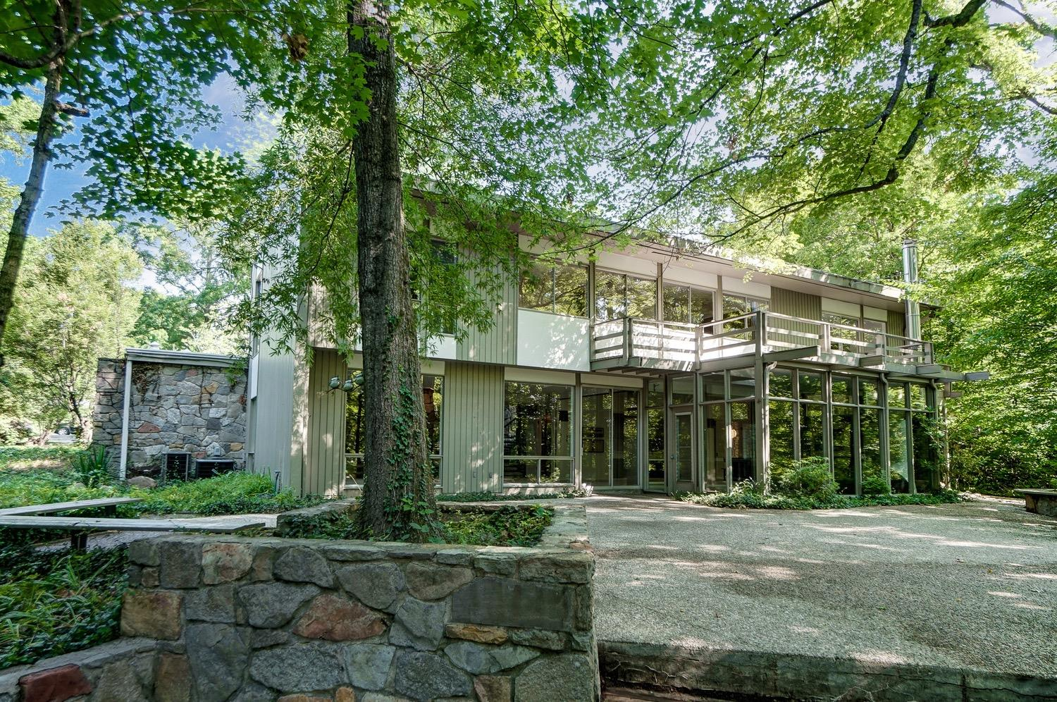 The rear of the home features plenty of windows to enjoy the views of the private wooded backyard and enormous patio and deck areas.