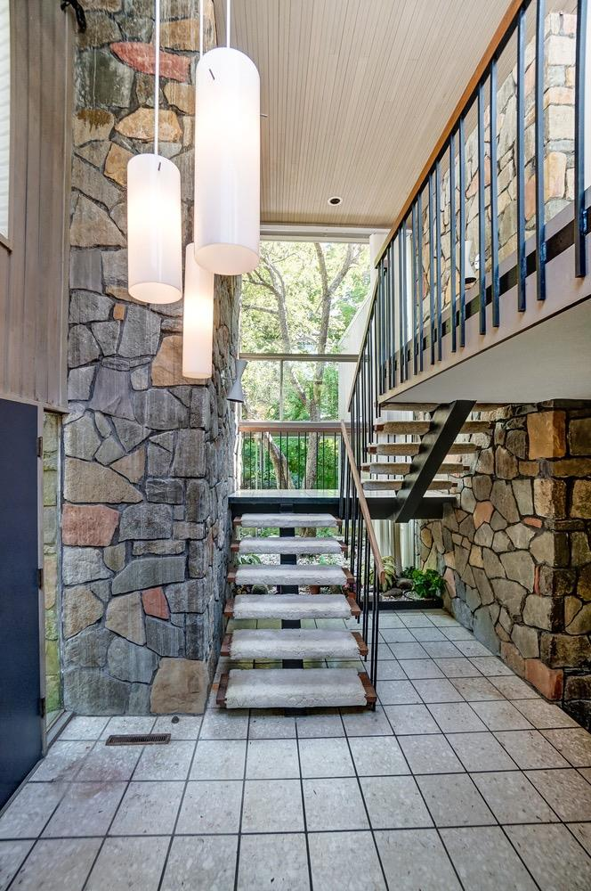 The floating stairway between textural stone walls overlooks the home's landscaping and covered outdoor walkways.