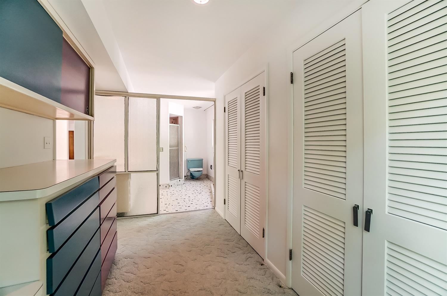 The primary dressing room features two more double closets and custom storage. The sliding dimpled translucent doors to the bath are everything.