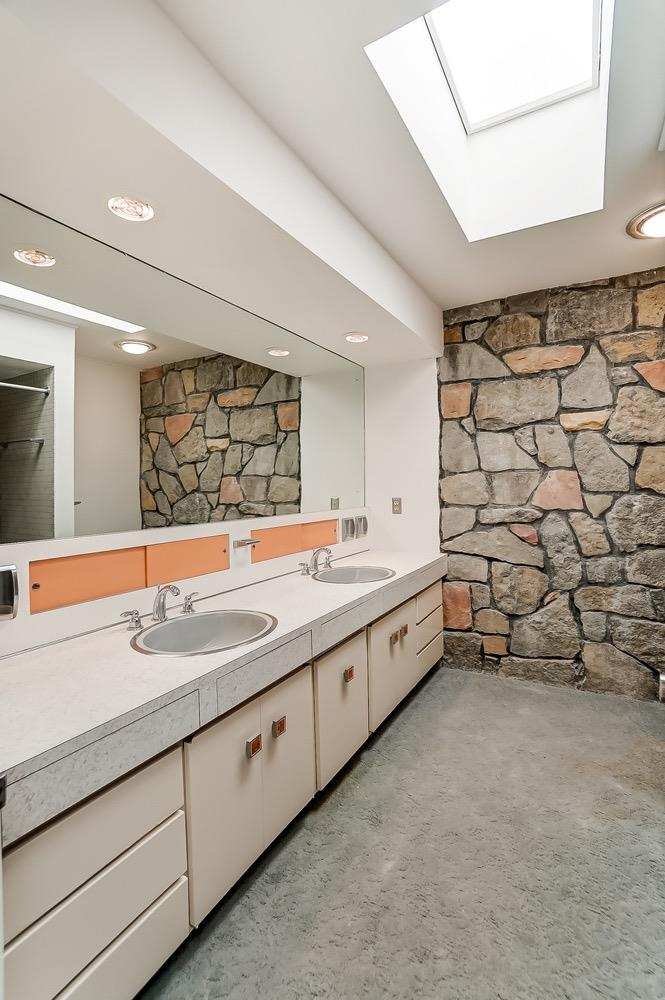 Check out this skylit second floor bath. The stone wall, colorful orange accents, tile and resin cabinet door knobs make it special and unique. Older carpeting over original mosaic tile floor.