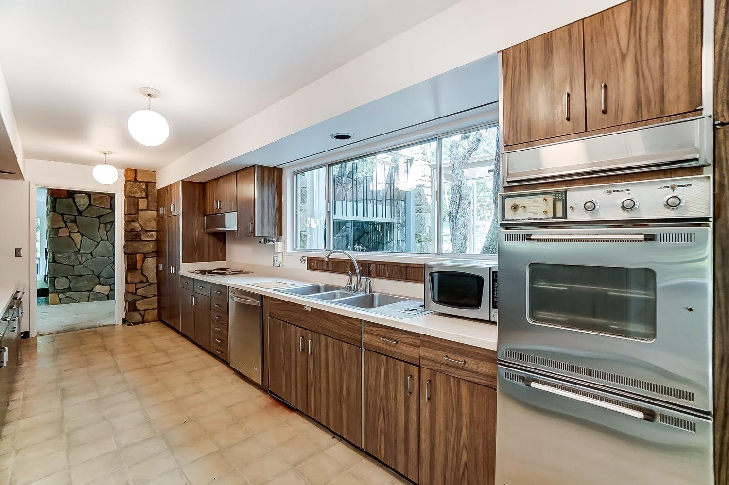 The time capsule kitchen features the original custom Mueller Company of Madeira wood grained laminate cabinets, many of the original stainless steel appliances plus a Nutone exhaust hood and remnants of the Nutone Food Center. What an incredible picture window above the sink!