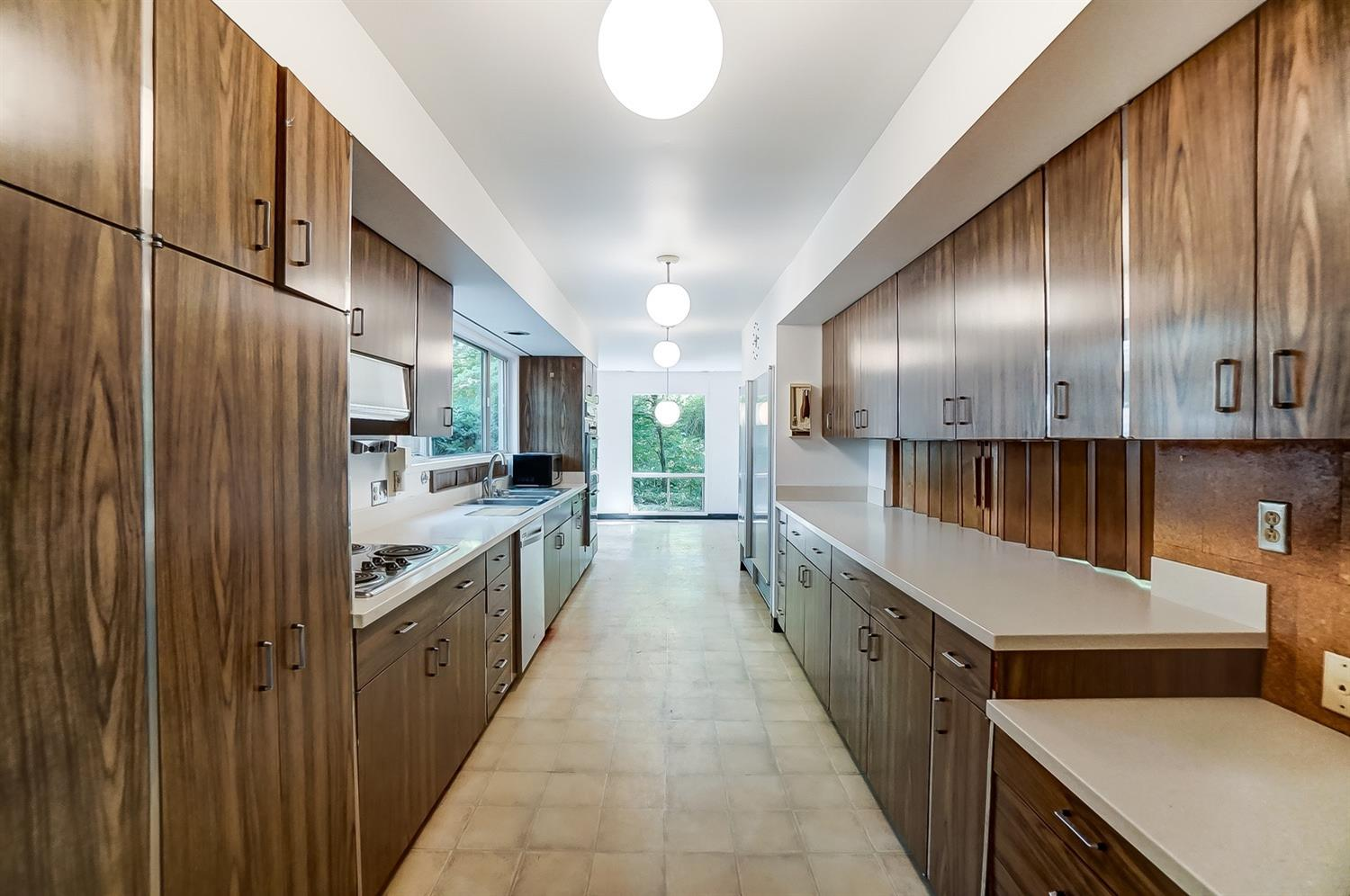 This vantage point show the kitchen's planning desk, the passthrough opening with accordion slider doors and opening breakfast room. Original vintage spherical lighting!