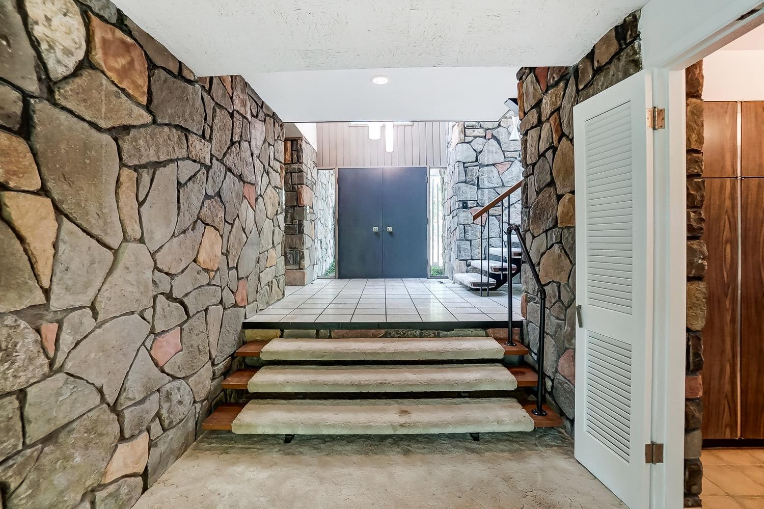 The entry hall follows the stone walls to step in the open living, family, and dining areas. The doorway to the right accesses the kitchen.