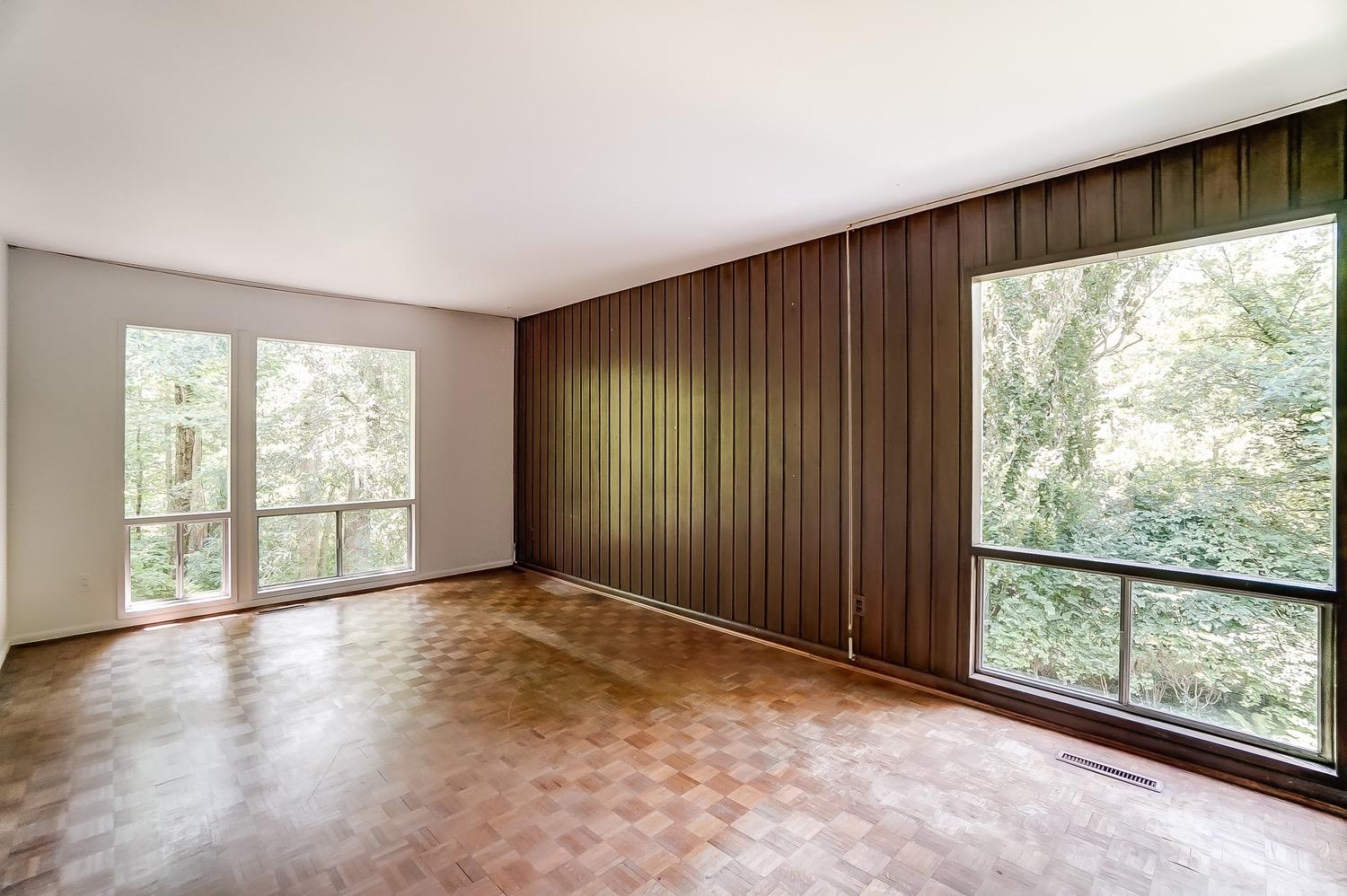 Bedroom features a wood paneled wall and could be used as an office or study.