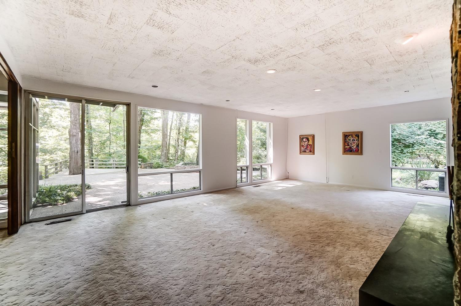 Light and bright living area with large expanses of glass and a sliding door to the rear patio/deck. The older wall-to-wall carpeting over a subfloor awaits your choice of new flooring.