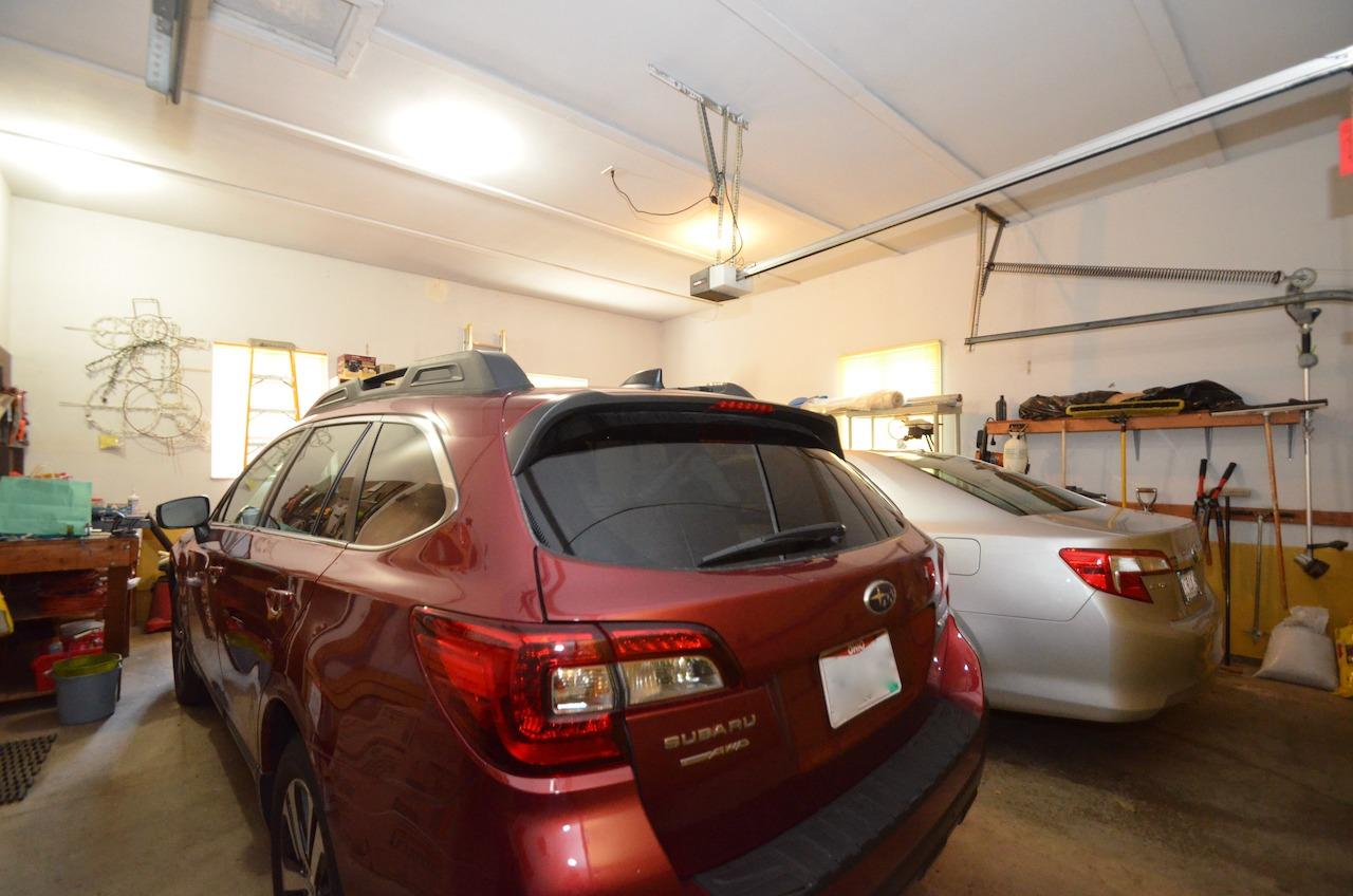 And here is the oversized 2 car garage.  It is TALL!  Like you could add a whole loft space in here or add a car lift to stack your sports cars! To the left of the red car is the door to the mudroom/laundry room with direct access to the kitchen.  Very convenient!!