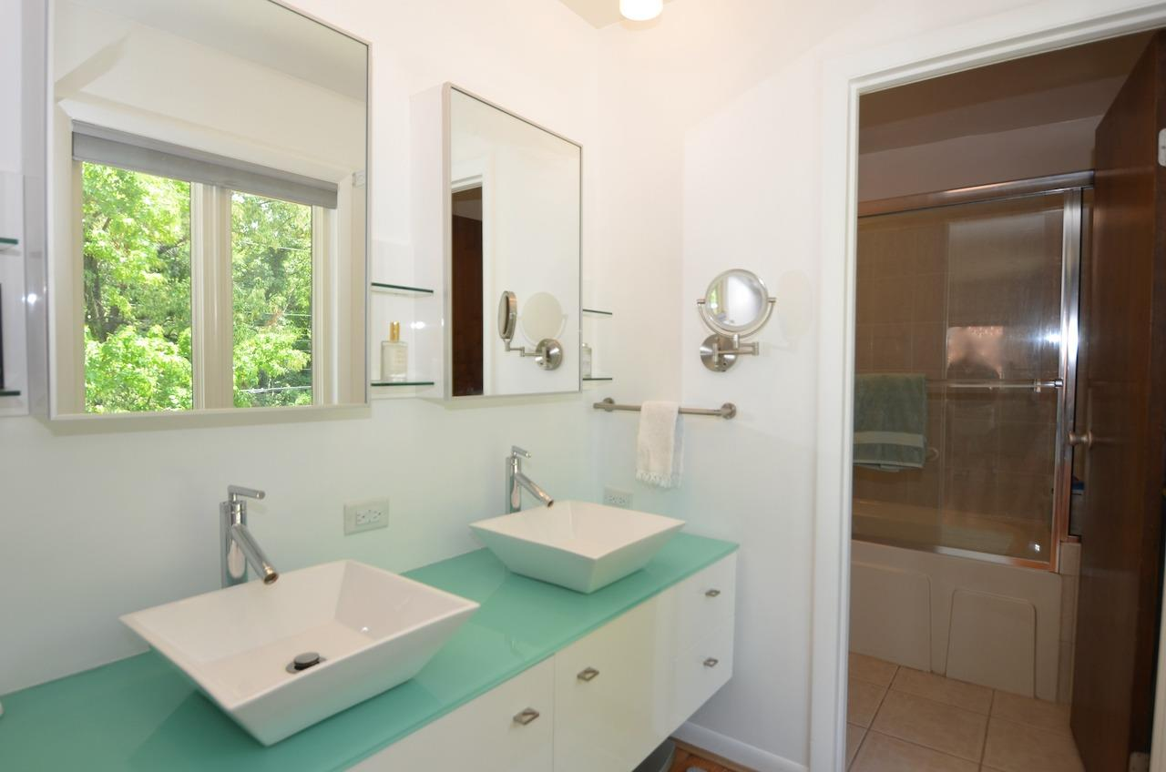 Dual sinks are in the outer space, and tub & toilet are in a separate compartment.