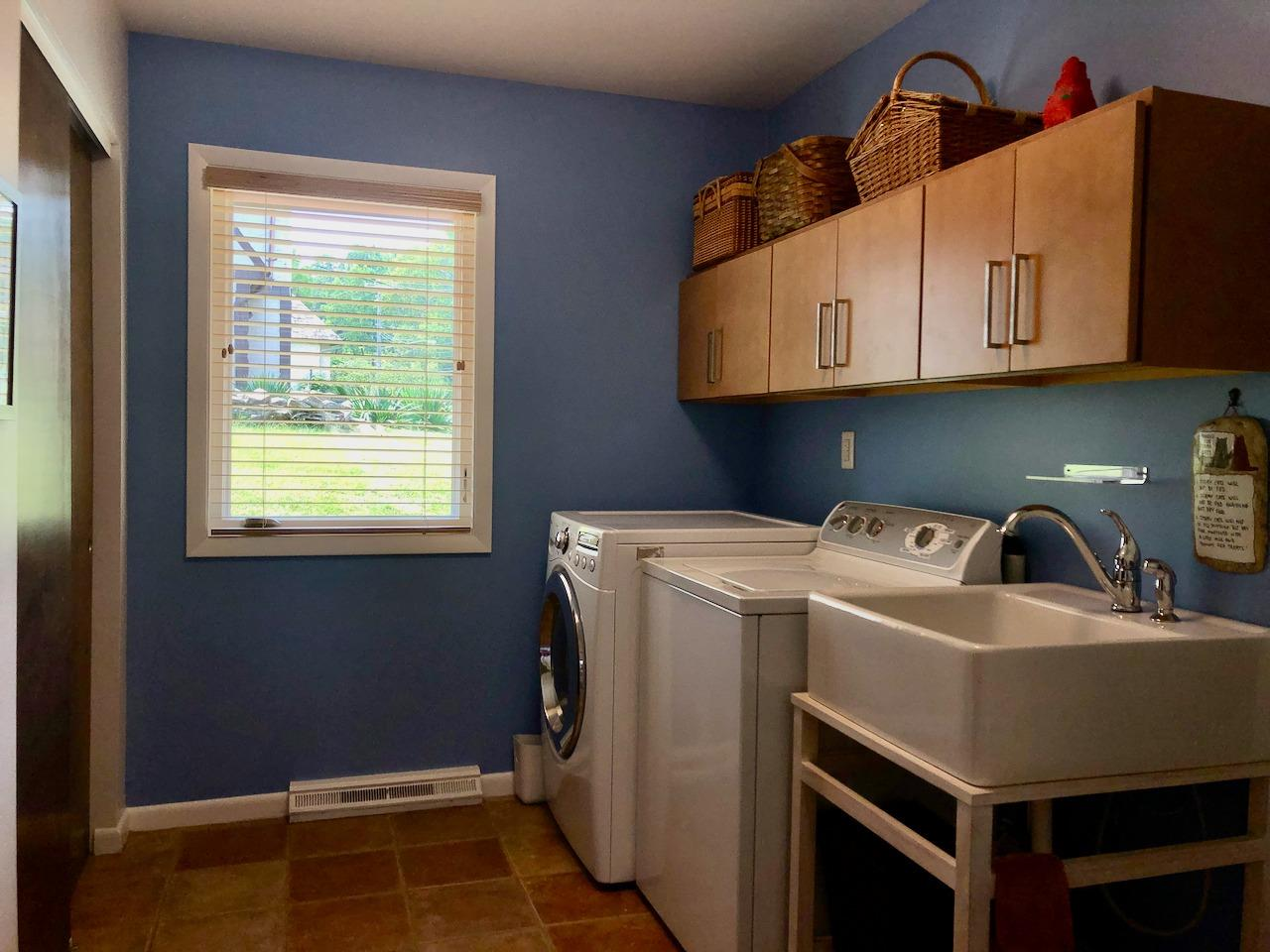 The laundry/mudroom is the perfect transition from the garage to the kitchen.  Such a handy space with 2 large closets, cabinets, washer & dryer (included in sale) and a laundry tub! And not just any laundry tub - it's a Villeroy & Boch contemporary farmhouse sink!  Door to the garage is just to the right of the sink.