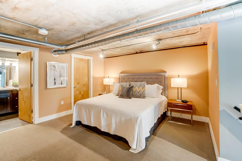 Lofted primary bedroom with en suite bath, walk-in closet, exposed ductwork, and sleek concrete ceilings