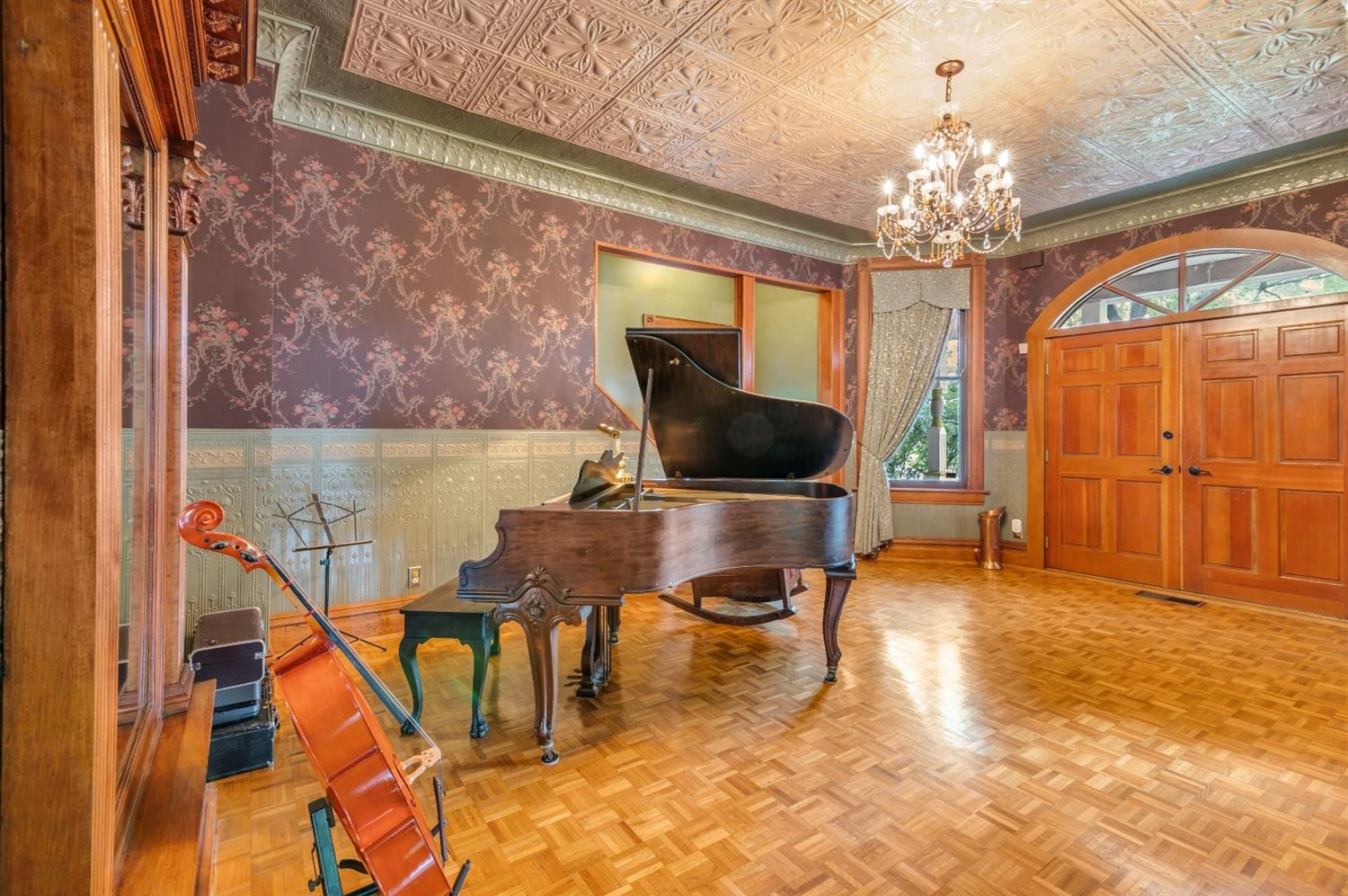 Stunning entry foyer with original tin ceiling, parquet floors and French doors.  This historic home has the original windows in the front of the house in this historic area, but the rest has replacement windows.