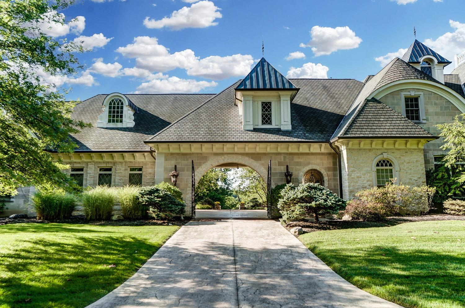 Gated entry into a porte cochere flanked by two 3-car garages covered with carriage styled doors.  Two garages are equipped with car lifts to store cars giving a total of 8-car storage.