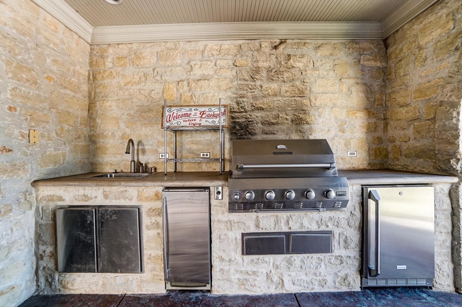 A covered stone outdoor kitchen equipped with a Frontgate grill, refrigerator, ice maker, prep sink and counter.