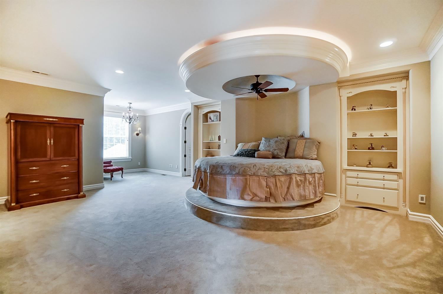 A guest room on the second floor features a circular bed, full bathroom, vanity area and large walk-in closet.