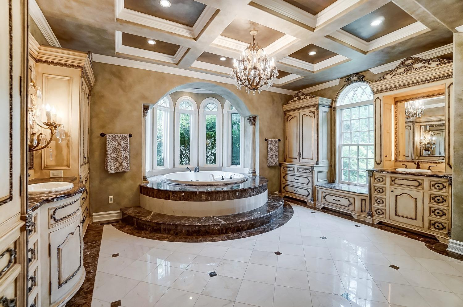 The master bathroom has a his-and-hers vanity area, a towel-warming drawer, all marble floors, a walk-in shower/steam room with seats, body sprays and rain heads and a two person