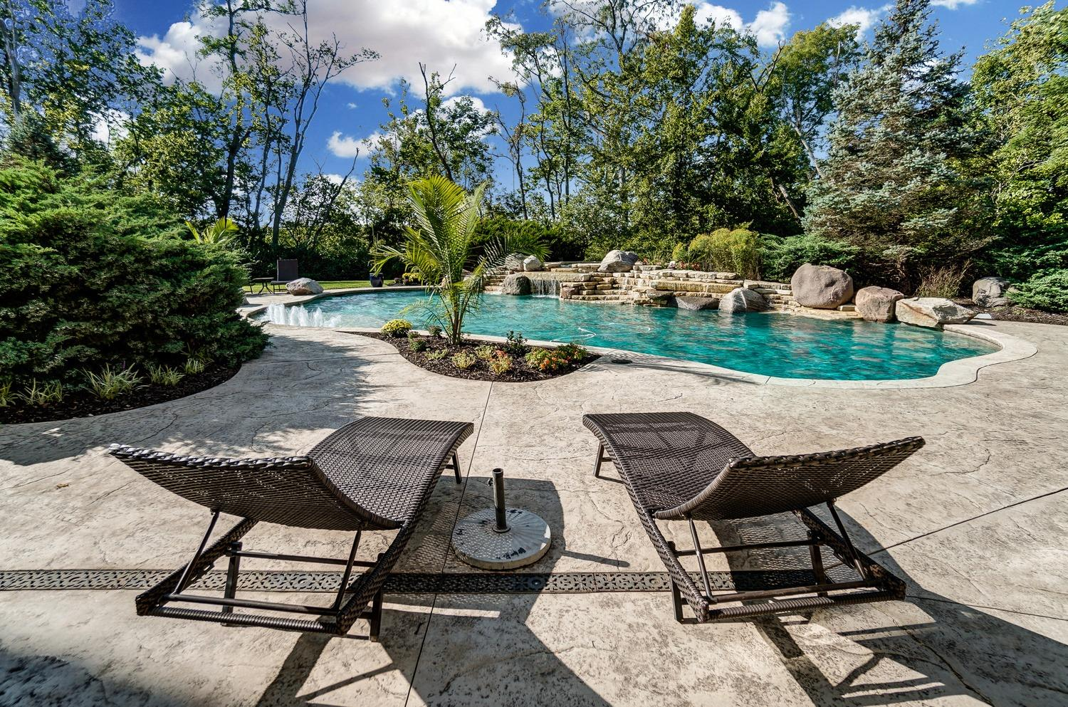 The heated, inground Gunite pool has a dramatic waterfall with an elevated inground hot tub with waterfalls.  There are water jets spraying up at the shallow entry into the pool and a deep end suitable for diving.